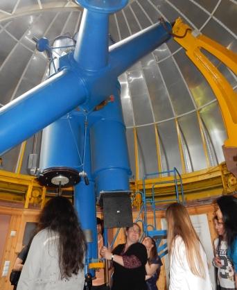 Stipendiaten lassen sich in der Kuppel der Sternwarte ein riesiges Teleskop erklären